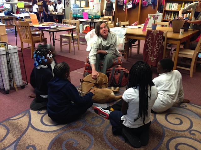 Beth Finke blind author and her seeing eye dog speaking to a small group of elementary school students in their school library
