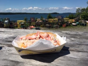 Photo of lobster roll on picnic table next to bay.
