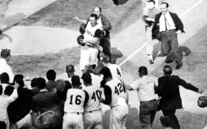 Photo of Bill Mazeroski being greeted by teammates as he arrives at home plate.