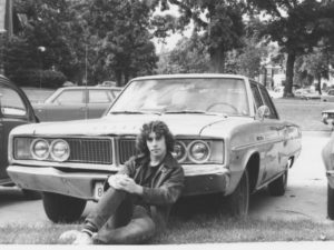 Photo of the author in a black leather jacket, sitting on the ground in front of his Dodge Dart.